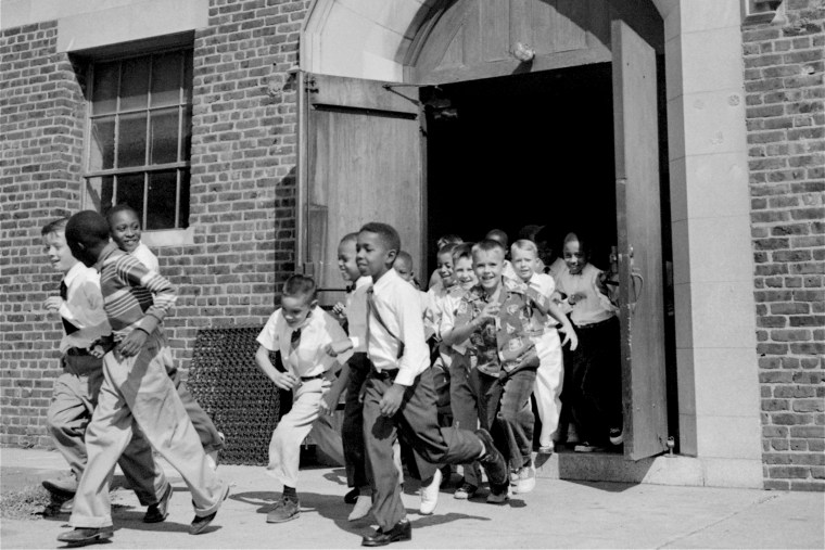 Black and white fourth graders at St. Martin School, Washington, DC, dash for the playground at recess, September 17, 1954.