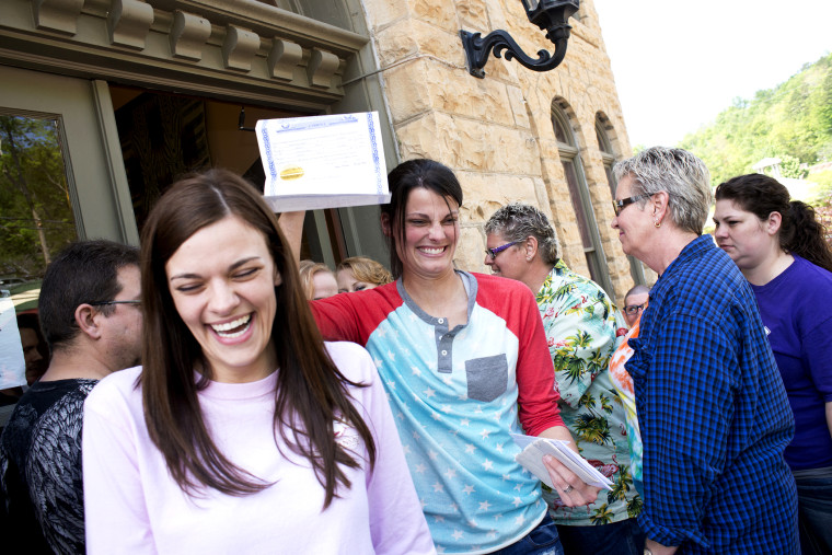 Kristin Seaton, of Jacksonville, Ark., holds up her marriage license as she leaves the Carroll County Courthouse in Eureka Springs, Ark., with her partner, Jennifer Rambo, May 10, 2014.