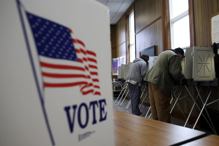 A man and woman cast their vote at a polling station on Nov. 6, 2012 in Sugar Creek, Wis.
