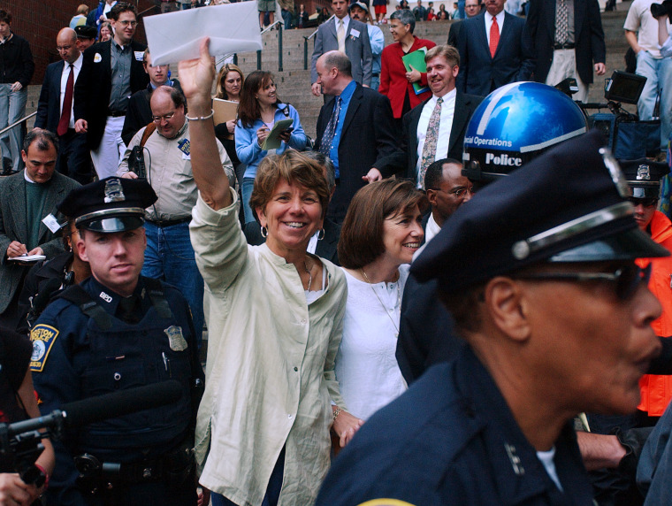 Hillary Goodridge holds up an envelope containing her marriage license as she leaves Boston City Hall with her partner Julie under a police escort in Boston, Monday May 17, 2004.