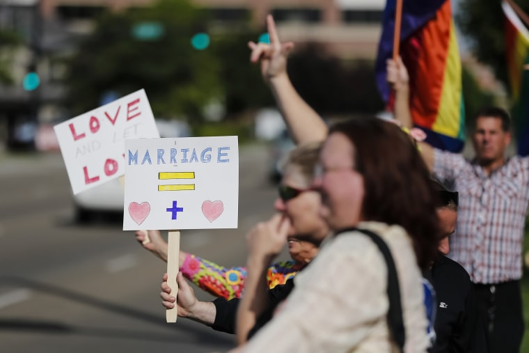 Gay marriage supporters hold up signs and rainbow flags for passing traffic at the Ada County Courthouse in Boise, Idaho, May 16, 2014.