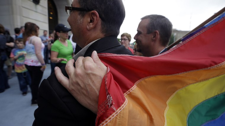 Shon DeArmon, right, puts his arm around his partner James Porter while holding a flag outside the Pulaski County Courthouse in Little Rock, Ark., May 12, 2014.