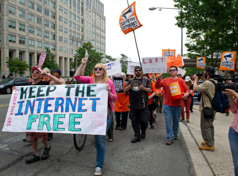 """Protesters hold a rally to support \""""net neutrality\"""" on May 15, 2014 at the FCC in Washington, D.C."""