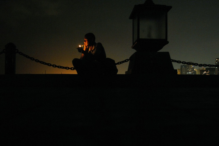 A man lights a cigarette at a seaside park in Manila, Philippines.