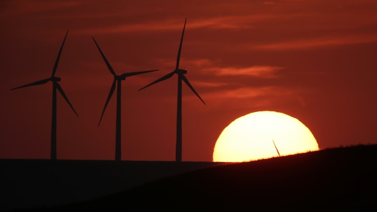 Wind turbines are silhouetted by the setting sun on Aug. 23, 2013, near Beaumont, Kan.