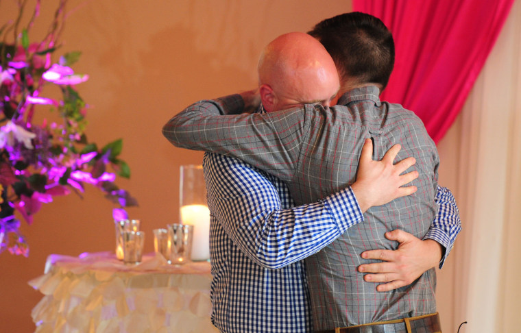 Jeff Salchenberg, left, hugs Paul Reinwand after getting married at the Melody Ballroom in Portland, Ore., on Monday, May 19, 2014.