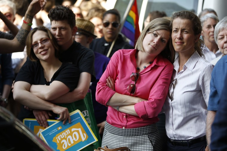 From right, Viola Vetterm and her wife Kate Potalivo, and Amber Orion and her partner, Joy Payton listen to a speaker during a rally at City Hall, on May 20, 2014, in Philadelphia.