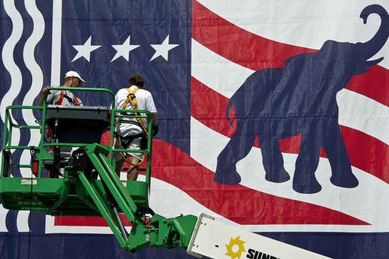 Workers mount a giant banner at the Tampa Bay Times Forum ahead of the Republican National Convention in Tampa, Florida, on Aug. 24, 2012.