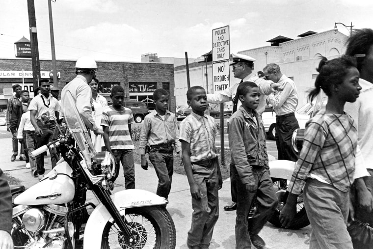 Policemen are lead a group of black school children into jail, following their arrest for protesting against racial discrimination near the city hall of  Birmingham, Ala., on May 4, 1963.