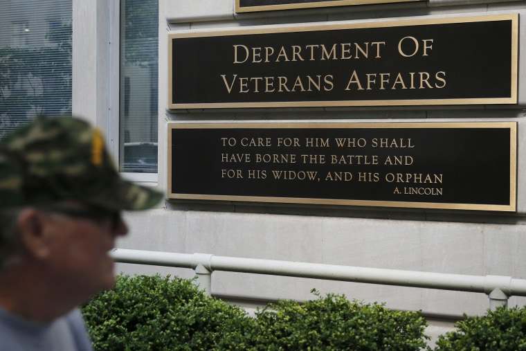 The sign in the front of the headquarters building at the Department of Veteran Affairs is seen as a man walks past in Washington