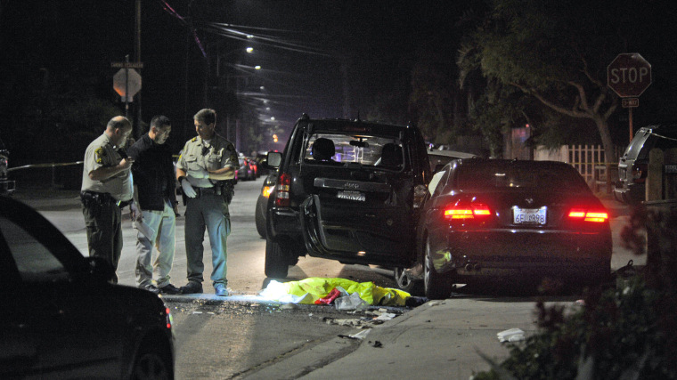 This image provided by the Santa Barbara Independent shows a body covered on the ground after a mass shooting near the campus of the University of Santa Barbara in Isla Vista, Calif., Friday, May 23, 2014.