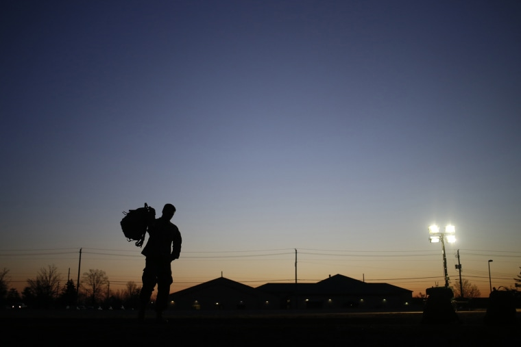 A soldier grabs his rucksack following a homecoming ceremony, Feb. 27, 2014, in Fort Knox, Ky.