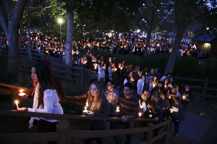 People gather at a park for a candlelight vigil to honor the victims of Friday night's mass shooting on Saturday, May 24, 2014, in Isla Vista, Calif.