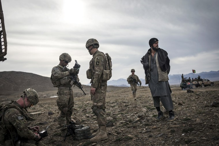 Soldiers from the 101st Airborne Division stand next to an Afghan suspected of Taliban connections in Lakaray, Afghanistan, April 14, 2013.