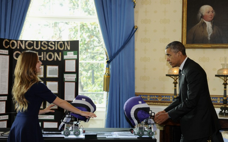 Maria Hanes, 19, of Santa Cruz, Calif., left, has President Barack Obama pull back a cushioned helmet as Obama toured the 2014 White House Science Fair exhibits that are on display in the State Dining Room of the White House in Washington, May 27, 2014.