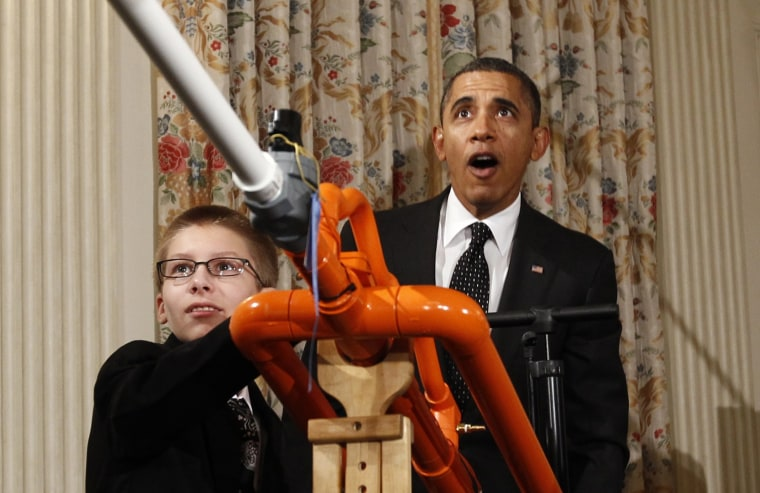 President Barack Obama reacts as Joey Hudy of Phoenix, Arizona, launches a marshmallow from his Extreme Marshmallow Cannon in the State Dining Room of the White House during the second White House Science Fair in Washington February 7, 2012.