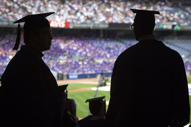 Graduates from New York University are silhouetted in the stands of Yankee Stadium during a commencement ceremony in the Bronx borough of New York.