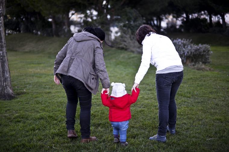 Same sex couple Olga Miranda (R) and Matilde Custodio (L) hold their daughter Carolina during a walk, February 23, 2014.