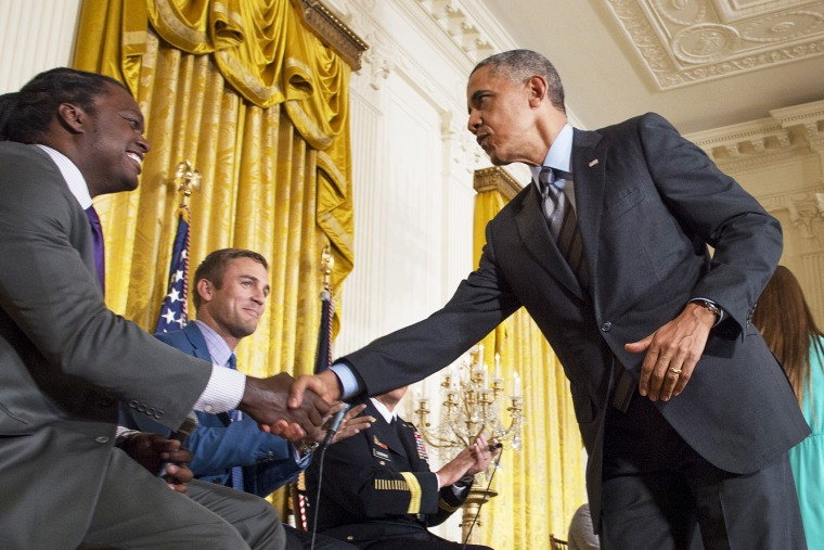 US President Barack Obama shakes hands with panelist and former NFL linebacker LaVar Arrington (L) during the White House Healthy Kids & Safe Sports Concussions Summit, May 29, 2014.