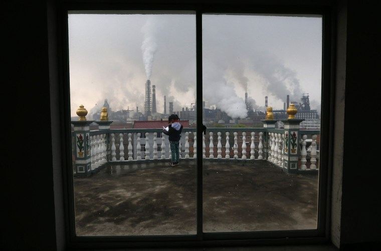 A girl reads a book on her balcony as smoke rises from chimneys of a steel plant, on a hazy day in Quzhou, Zhejiang province in this April 3, 2014 file photo.