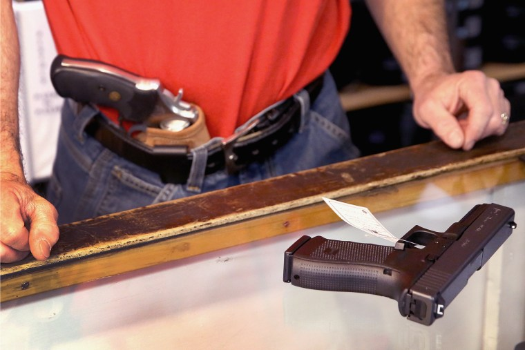 Dan Egar helps a customer shop for a handgun on February 13, 2014 in Tinley Park, Illinois.