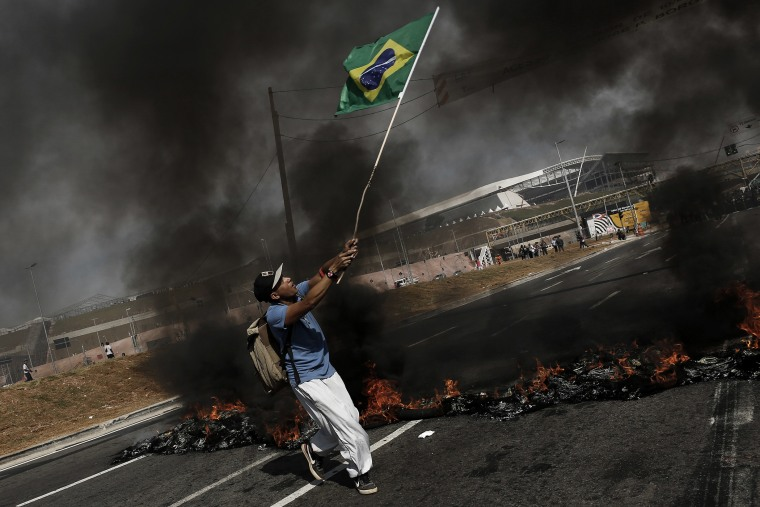 A man carries a flag of Brazil during a protest against the World Cup in Sao Paulo.