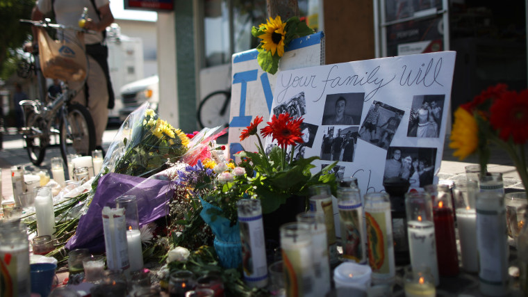 Photos of a victim stand in a makeshift memorial in front of the IV Deli May 25, 2014 in Isla Vista, California.