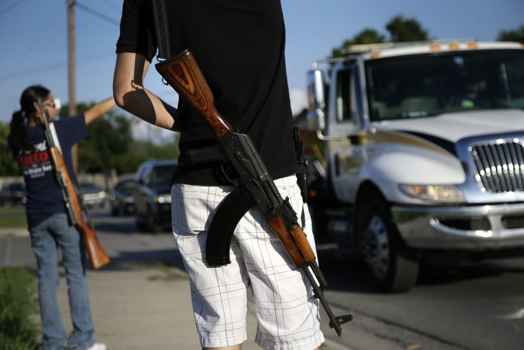 An open carry advocate carries his Romanian AK 47 over his shoulder during a demonstration, on May 29, 2014, in Haltom City, Texas.