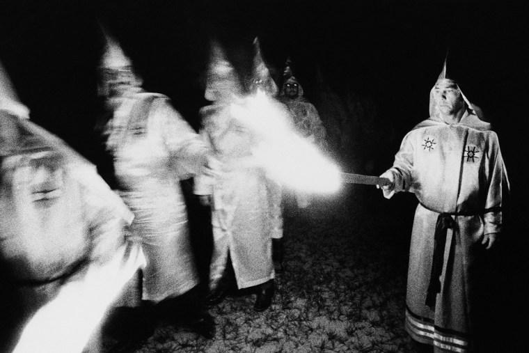 Ku Klux Klan members light their torches during a membership rally in Pensacola, Florida, May 25, 1975.