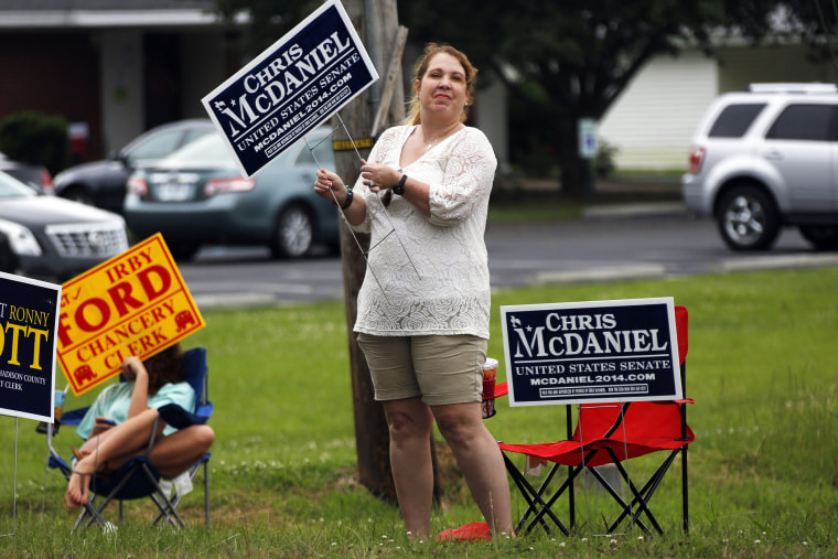 A woman waves her campaign sign for state Sen. Chris McDaniel, who is running against incumbent U.S. Sen. Thad Cochran in the GOP primary, June 3, 2014, in Madison, Miss.