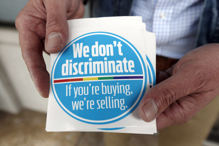 Eddie Outlaw, a Jackson hair salon owner, displays the stickers he and some other business owners display and have distributed to others in a show of support for gay and lesbian customers, on April 22, 2014, outside his business in Jackson, Miss.