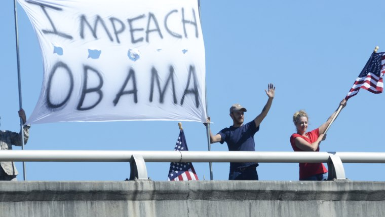 "In this photo taken Friday, October 11, 2013, Doug Bearden, Jonathan Branyon and Christine Reno, from left, wave flags and hold an ""Impeach Obama"" sign"