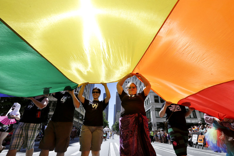 Marchers in Seattle's annual Gay Pride Parade carry a giant rainbow flag on June 30, 2013.