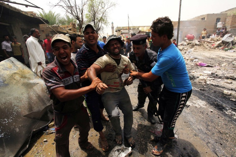 Men react at the site of a car bomb attack at a market in the town of Iskandariya