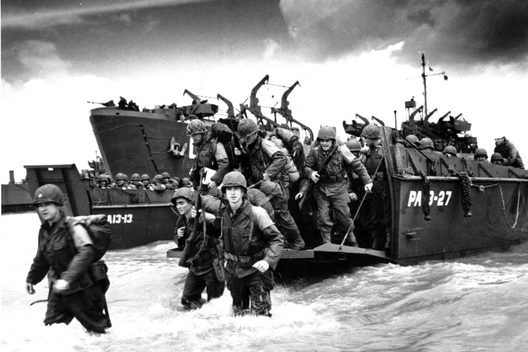 American reinforcements arrive on the beaches of Normandy from a Coast Guard landing barge into the surf on the French coast on June 23, 1944 during World War II.