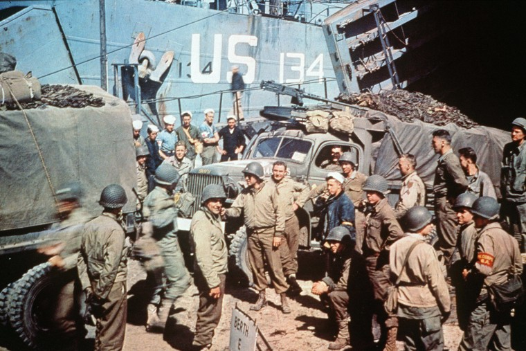 US soldiers gather around trucks disembarking from landing crafts shortly after Allied forces stormed the Normandy beaches, June 6, 1944.