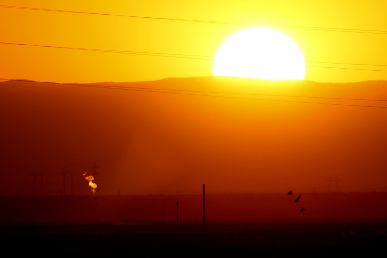 Gas is flared as waste (L) from the Monterey Shale formation where gas and oil extraction using hydraulic fracturing, or fracking, is on the verge of a boom, as the sun sets on March 22, 2014 near Buttonwillow, Calif.