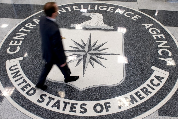 A man crosses the Central Intelligence Agency (CIA) logo in the lobby of CIA Headquarters in Langley, Virginia.