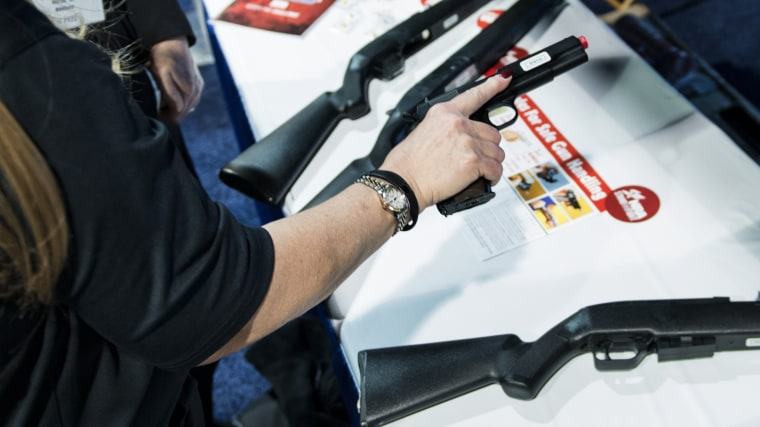 An instructor shows the proper way to hold a hand gun at an National Rifle Association virtual shooting booth during the American Conservative Union Conference March 6, 2014 in National Harbor, Maryland.