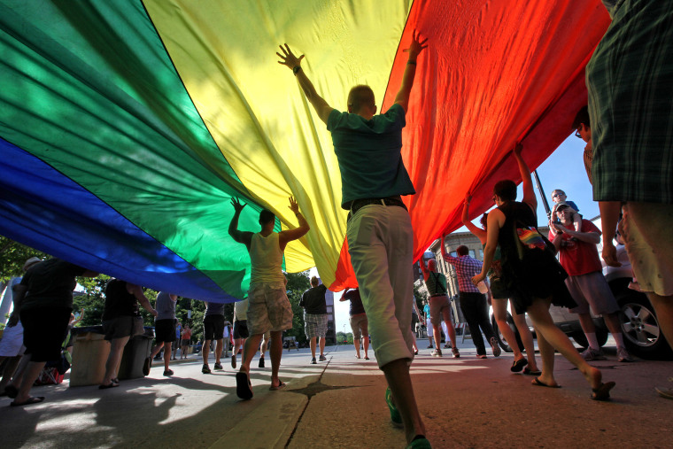 Supporters of a U.S. Supreme Court ruling which overturns the federal Defense of Marriage Act (DOMA) carry a large rainbow flag during a parade around the Wisconsin State Capitol in Madison, Wis. Wednesday, June 26, 2013.