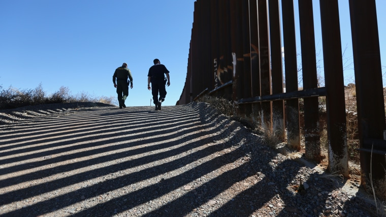 U.S. Customs and Border Protection personnel walk along a section of the recently-constructed fence at the U.S.-Mexico border on Feb. 26, 2013 in Nogales, Ariz.