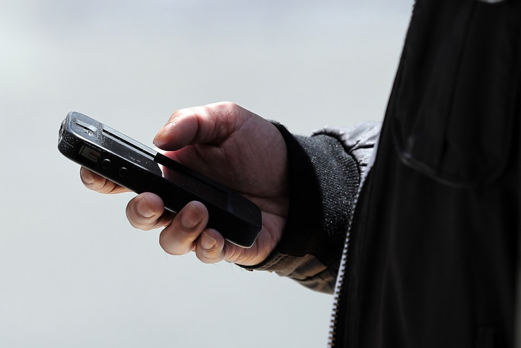 A pedestrian uses a smartphone as he walks along Market Street on June 5, 2013 in San Francisco, California.