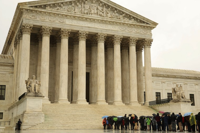 People line up in the rain outside of the U.S. Supreme Court in Washington April 29, 2014.