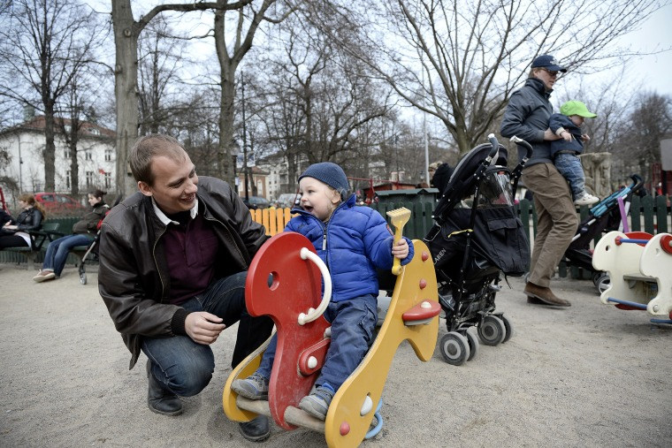 Swede Set Moklint plays with his kid Wilhelm during his paternity leave at Humlegarden park in Stockholm on April 24, 2013.