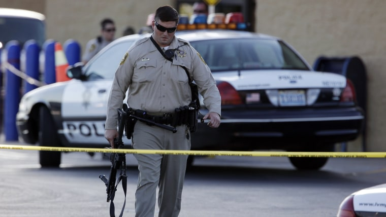 A Las Vegas police officer walks away from the scene of a shooting near a Wal-Mart, Sunday, June 8, 2014, in Las Vegas.