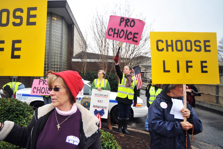 People supporting and opposing abortion demonstrate outside of the Alabama Women's Center for Reproductive Alternatives in Huntsville, Ala., Feb. 23, 2013.