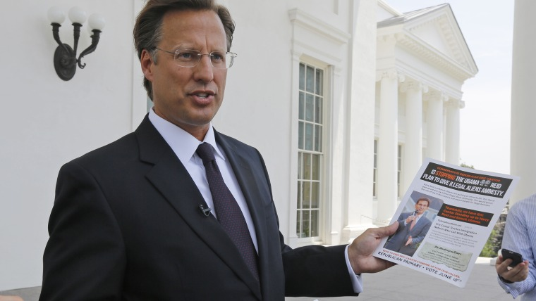 Seventh District US Congressional Republican candidate, David Brat displays an immigration mailer by Congressman Eric Cantor during a press conference at the Capitol in Richmond, Va., Wednesday, May 28, 2014.