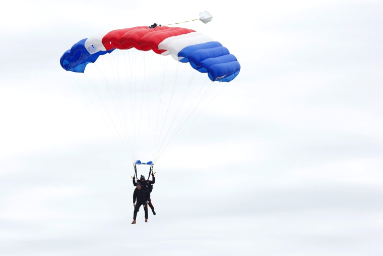 Former U.S. President George H.W. Bush and Mike Elliott, US Army Sergeant 1st Class (ret), jump out of a helicopter and parachutes down to St. Anne's Episcopal Church on June 12, 2014 in Kennebunkport, Maine.