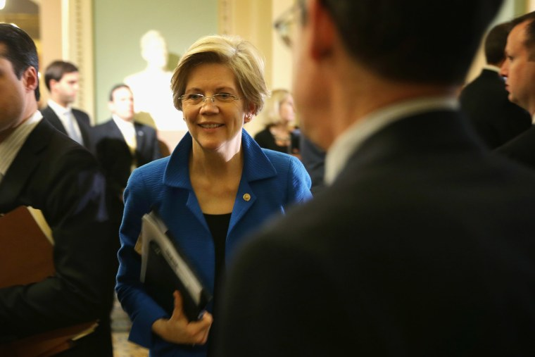 U.S. Sen. Elizabeth Warren (D-MA) (C) walks towards the Senate Chamber after a policy luncheon May 6, 2014 on Capitol Hill in Washington, DC.