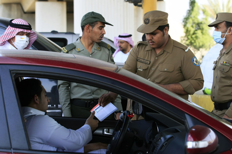 In this file photo taken Friday, Nov. 12, 2010, a Saudi policeman checks identity papers of pilgrims at a checkpoint outside Mecca, Saudi Arabia.
